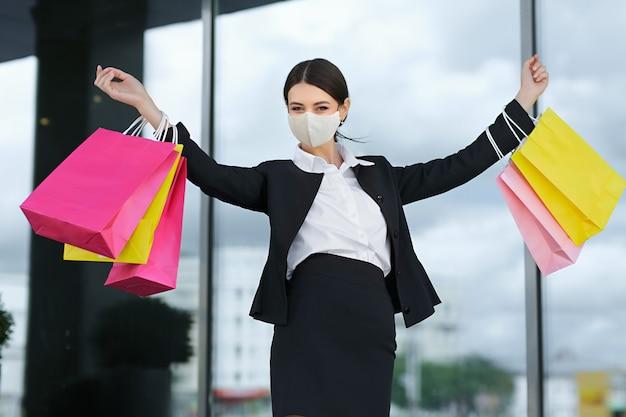 カラフルなバッグを持ったビジネススーツを着た女の子が、ショッピングセンターの近くでたくさんの売り上げを上げ、手を上げて購入品を披露しました。