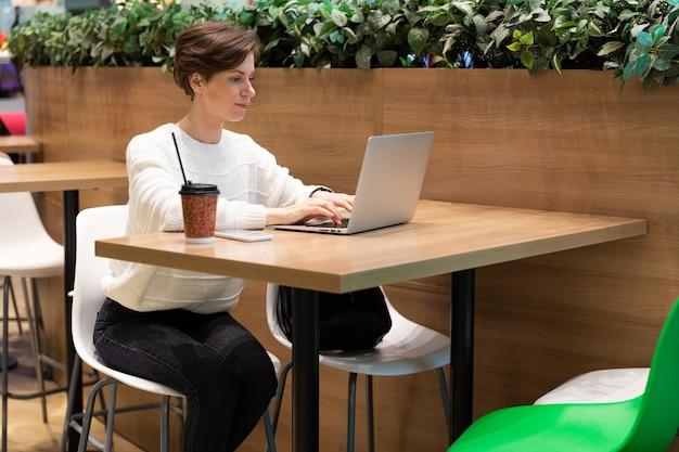 카페에서 한 소녀가 회의를 위해 파트너를 기다리고 있으며 노트북 앞의 테이블에 앉아 있습니다.