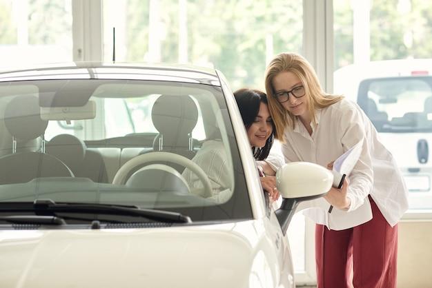 Девушка в автосалоне покупает небольшую городскую машину.