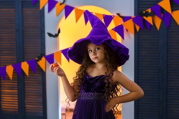 Девушка в карнавальном костюме ведьмы и фиолетовой шляпе держит в руке маленькую тыкву