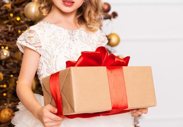 Девушка в шикарном платье стоит с новогодним подарком в руках на фоне новогодней елки
