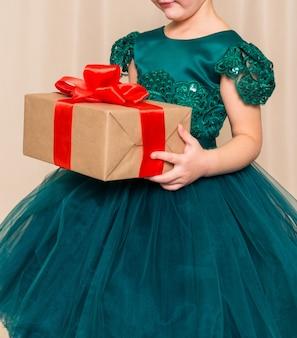 Девушка в шикарном зеленом платье стоит с новогодним подарком в руках на фоне