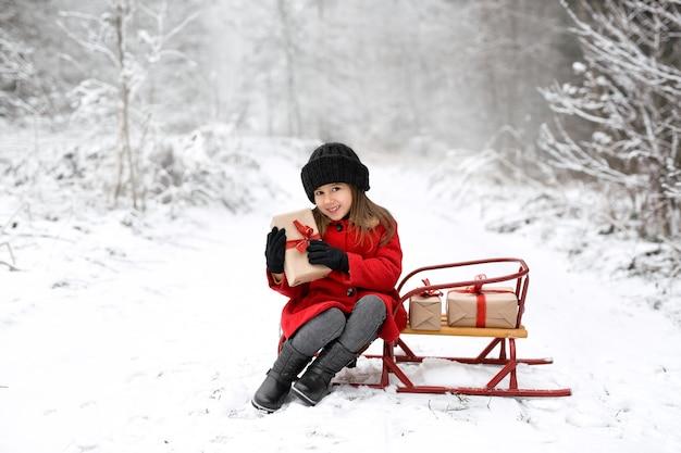 コートとニット帽の女の子が手にクリスマスプレゼントを持ってそりに座っています