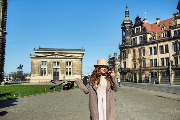 Девушка в пальто и шляпе на улице города дрездена. саксонская швейцария, германия.
