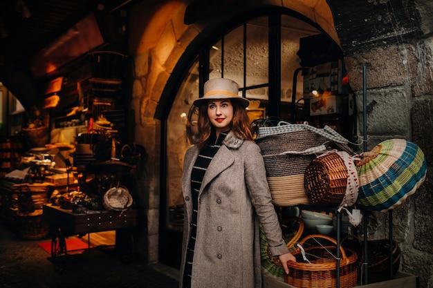 アヌシーの旧市街のバスケットの近くにコートと帽子をかぶった女の子が立って、屋外でヨーロッパの街を探索しています。