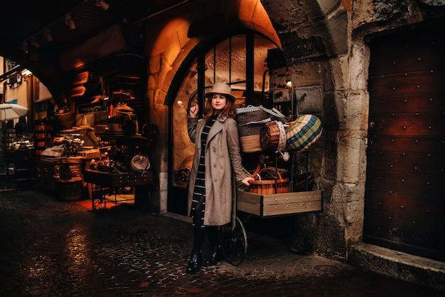 코트와 모자를 입은 소녀가 안시의 구시 가지 바구니 근처에 서서 야외에서 유럽 도시를 탐험하며 시간을 보냅니다.