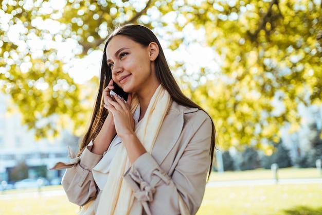 코트를 입은 소녀가 전화를 걸고 있습니다. 가을 풍경