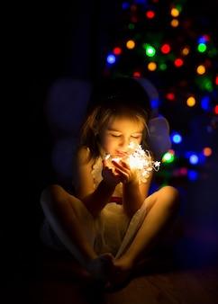 彼女の手に明るいクリスマスライトを持つ暗い部屋の女の子