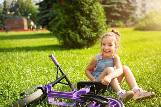 Девушка в джинсовом комбинезоне катается на фиолетовом беговом велосипеде летом в зеленом парке