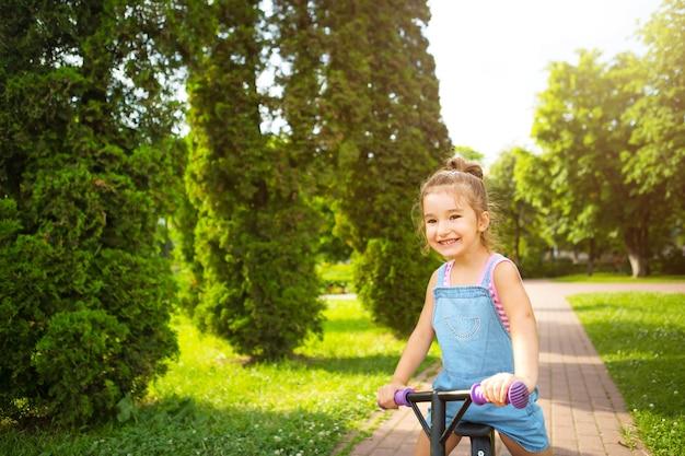 Девушка в джинсовом комбинезоне летом катается на фиолетовом беговом велосипеде