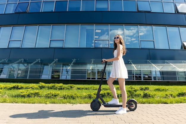 ドレスを着た女の子が近代的な建物の近くで電動スクーターに乗る