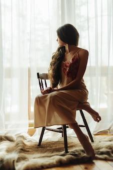 Девушка в халате сидит возле окна