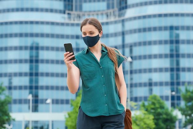 얼굴 마스크의 소녀가 시내의 스마트 폰에서 뉴스를 읽고 있습니다.