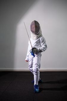 Девушка в фехтовальном костюме с мечом в руке. молодые девушки модели практикуют и тренируются. спорт, здоровый образ жизни.