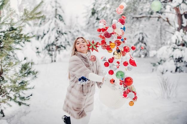 Девушка в шубе кидает елочные шары, чтобы украсить елку. девушка бросает елочные игрушки из корзины в зимний лес.