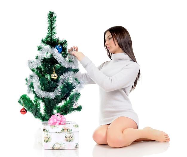 회색 드레스를 입은 소녀가 크리스마스 트리와 선물 근처 바닥에 앉아있는 동안 아래를 내려다 보면서 포즈를 취합니다.