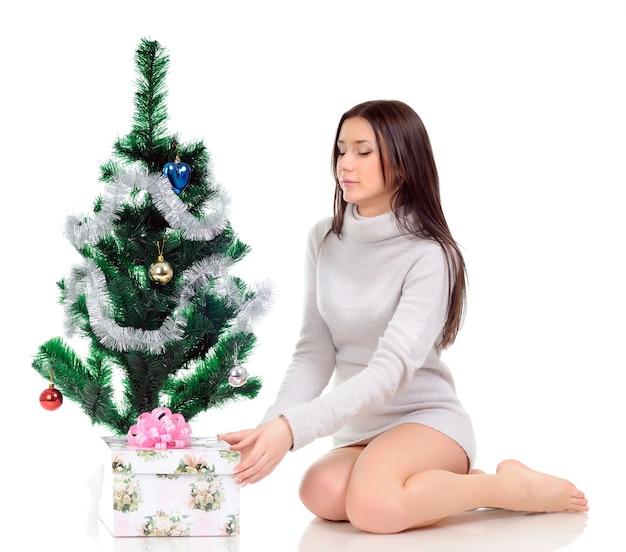 Девушка в сером платье смотрит вниз и позирует, сидя на полу возле новогодней елки и подарка
