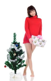 Девушка в сером платье смотрит вниз и позирует, стоя на полу возле новогодней елки и подарка