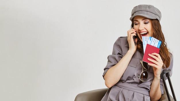 회색 드레스를 입은 소녀가 전화로 말하고 비행기 티켓과 여권을 가지고 있습니다.