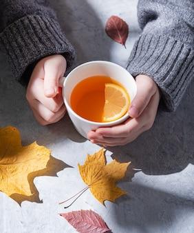 Девушка в сером свитере держит в руке чашку чая с лимоном на сером фоне. утренний свет. вид спереди и крупным планом