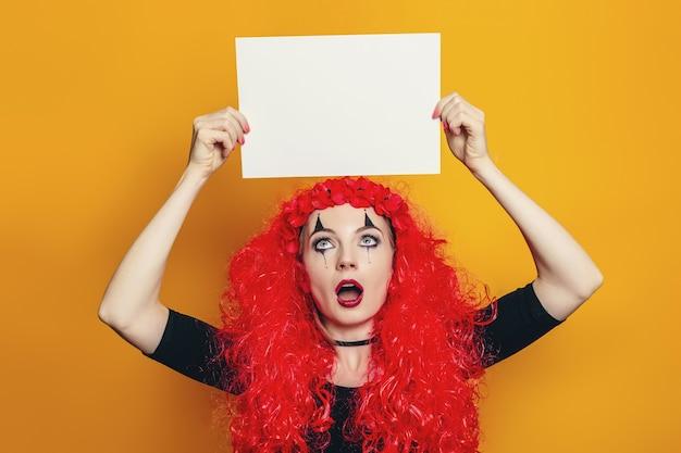 ハロウィーンの衣装を着た女の子が頭上に一枚の紙を持っています
