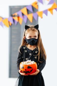 マスクをつけたハロウィンコスチュームの女の子がおやつでいっぱいのカボチャを持っています