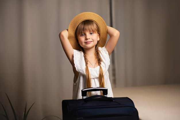 모자를 쓴 소녀와 짐이 든 가방이 손에 든 여행 가방이 호텔 방에 있습니다. 호텔 여행에서 체크인하고 바다 휴식을 취합니다.