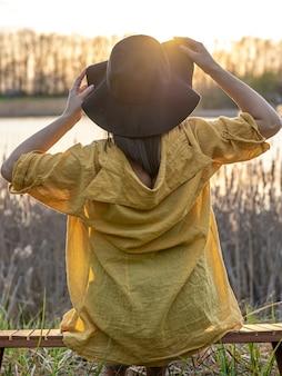 Девушка в шляпе и в стиле casual сидит на скамейке у озера на закате