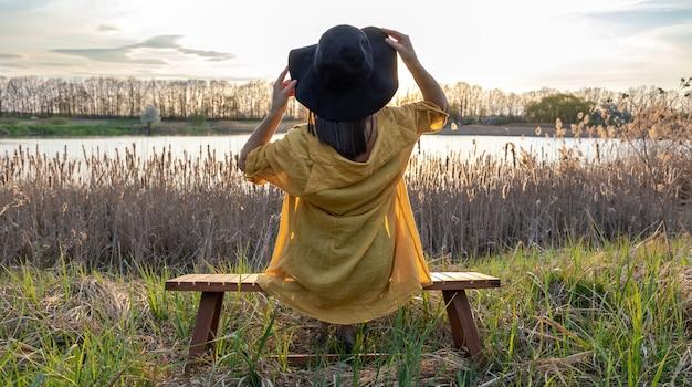 帽子をかぶったカジュアルなスタイルの女の子が日没時に湖の近くのベンチに座っています