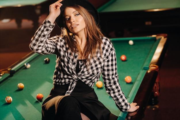 ビリヤードクラブの帽子をかぶった女の子がビリヤード台に座っています。プールで遊んでいます。