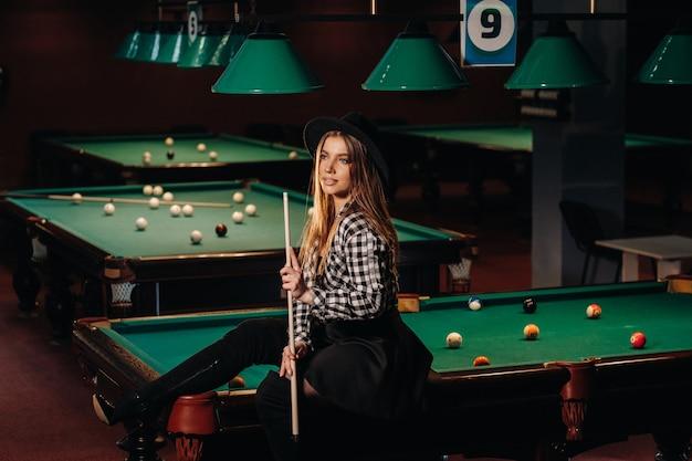 ビリヤードクラブの帽子をかぶった女の子が手にキューを持ってビリヤードテーブルに座っています