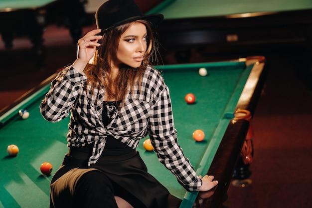ビリヤードクラブの帽子をかぶった女の子がビリヤード台に座っています