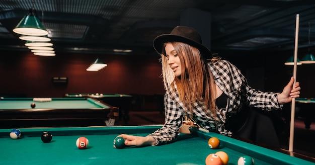 手にキューとボールを持ったビリヤードクラブの帽子をかぶった女の子。プールで遊ぶ。