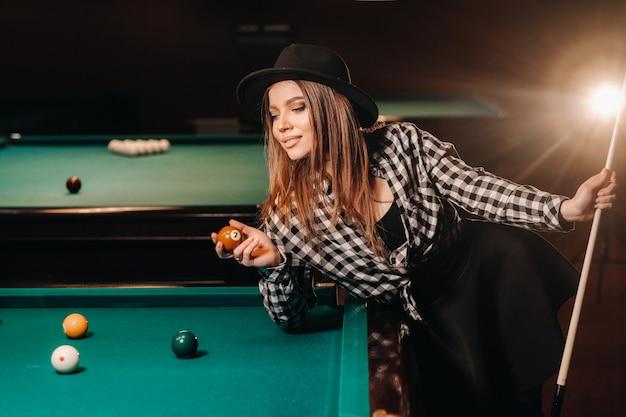手にキューとボールを持ったビリヤードクラブの帽子をかぶった女の子