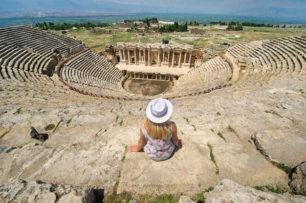 모자를 쓴 소녀가 터키 파묵칼레의 히 에라 폴리스 폐허에있는 로마 원형 극장에 앉아 있습니다.
