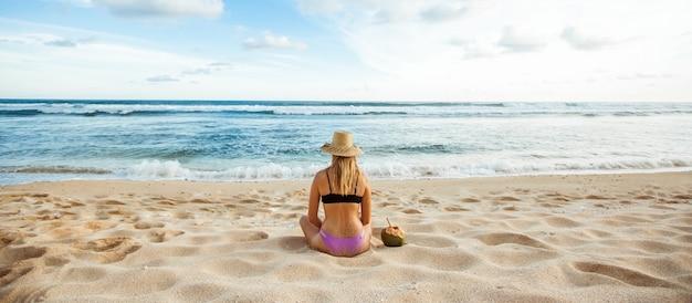Девушка в шляпе сидит на белом песке спиной к камере и смотрит на океан, рядом с ней кокосовый орех banner panorama