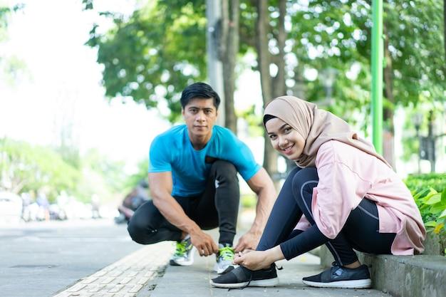 Девушка в платке и мужчина улыбаются, готовясь поправить шнурки перед бегом в парке.