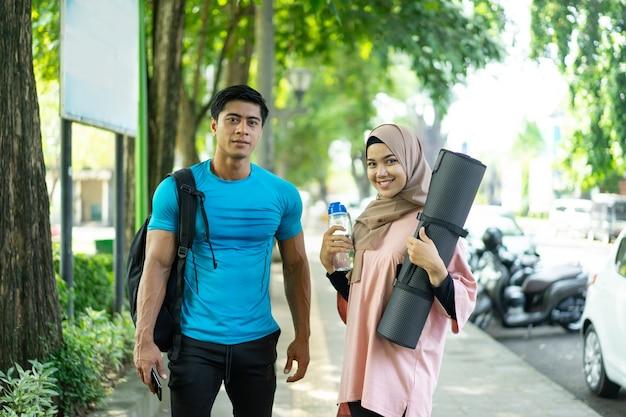Девушка в платке приносит матрас и бутылку с водой, а мужчина с рюкзаком улыбается, готовясь к занятиям спортом на открытом воздухе в парке.