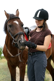 Девушка в шлеме и снаряжении для верховой езды общается со своим пегим конем