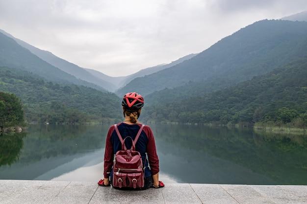 헬멧을 쓴 소녀가 산기슭의 호수 옆에 앉아 있었다