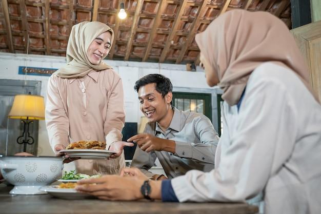 Девушка в хиджабе готовит и приносит тарелку жареного цыпленка, чтобы вместе съесть их в столовой.