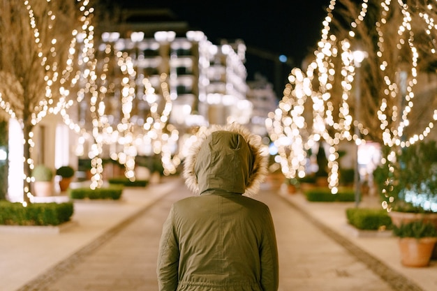 Девушка в капюшоне с мехом стоит на улице, украшенной к рождеству в городе. фото высокого качества