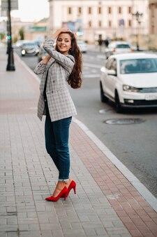재킷을 입고 긴 머리를 한 소녀가 오래된 도시를 걷고, 아름다운 소녀가 미소를 짓고, 소녀가 길을 걷고있다.