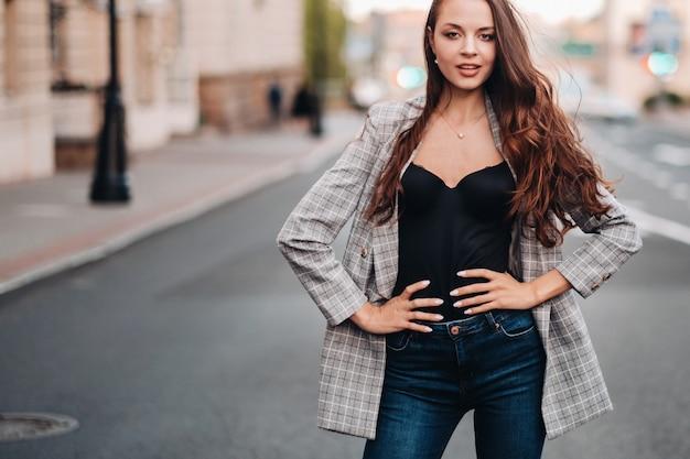 Девушка в куртке и с длинными волосами идет по старому городу. красивая девушка улыбается. девушка на дороге.