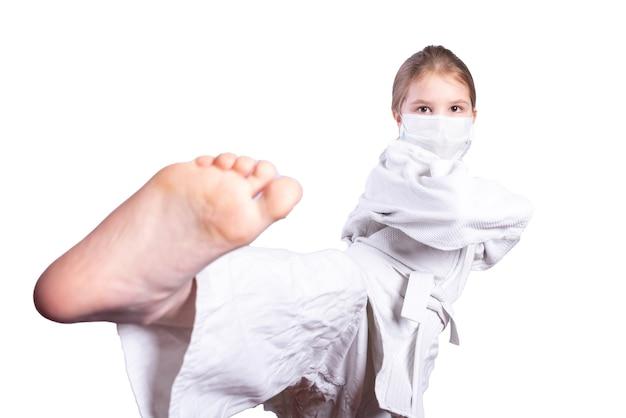 柔道着物の女の子と医療用マスク。彼は蹴ります。白い背景で隔離。高品質の写真