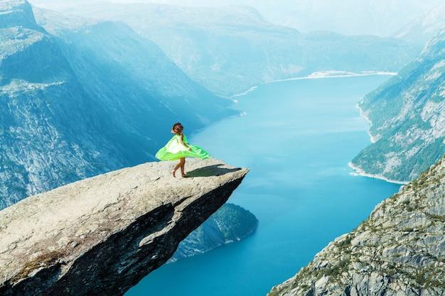 Девушка в светло-зеленом платье танцует на тролльтунге в норвегии