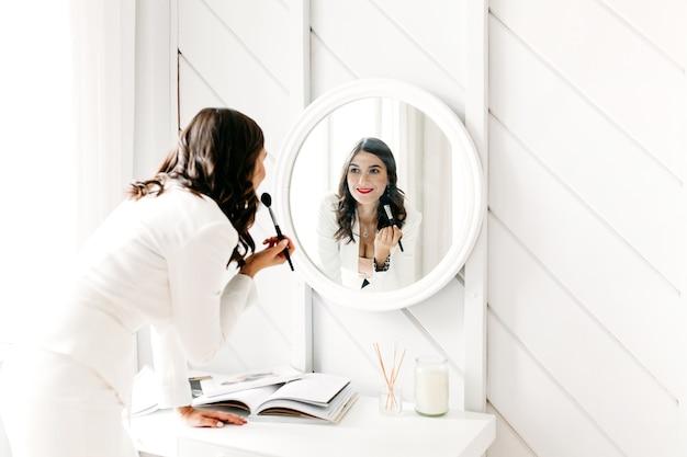 Девушка в светлом костюме с темными волосами стоит перед зеркалом и наносит макияж