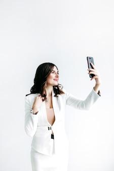 黒髪の薄手のスーツを着た女の子が写真を撮る