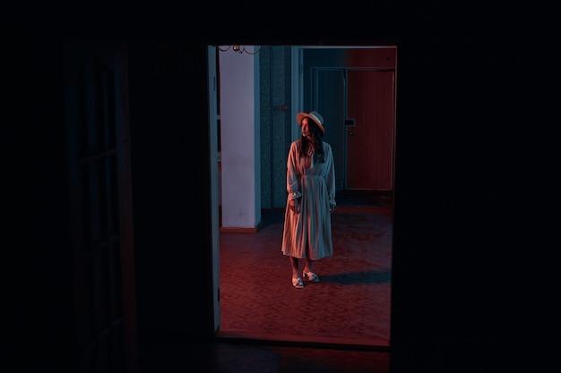 長いシフォンドレスと帽子をかぶった女の子が暗い部屋に立っています。赤いネオン照明でクリエイティブな撮影。高品質の写真