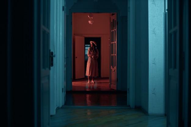 긴 드레스를 입은 소녀가 오래된 집의 어두운 복도 끝에 서 있습니다. 창조적 인 사진 촬영 redtinted 사진 촬영 고품질 사진